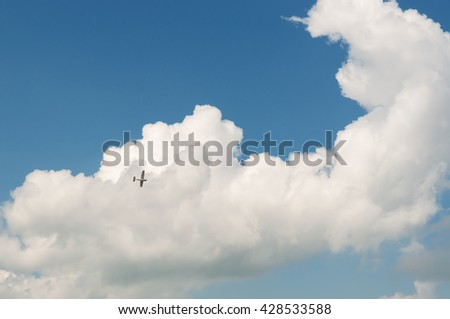 Aeroplane an2 in the blue sky with big white cloud - stock photo