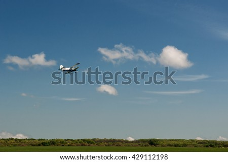Aeroplane an2 in the blue sky with white clouds - stock photo