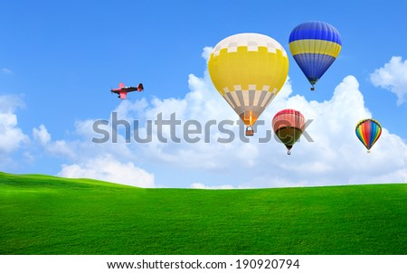 Aeroplane and Hot air balloon floating in the sky over green grass - stock photo