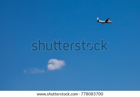 Aeroplane and white cloud on blu sky. Travel Concept.