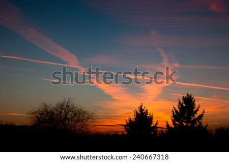 Aeroplane contrails warm sunset light on dark blue sky and tress silhouette in Poland, Europe, Nobody, horizontal orientation. - stock photo