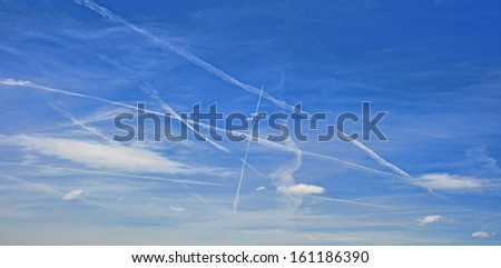 Aeroplane vapour trails showing busy flight path over the UK - stock photo