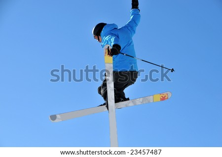 Aeroski: skier in blue jacket doing a helicopter jump high in the sky