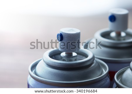 Aerosol spray cans nozzle close up. Several spray cans with light in background. Shallow depth of field. - stock photo