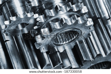 aerospace titanium and steel gears and cogs, engineering parts in blue - stock photo