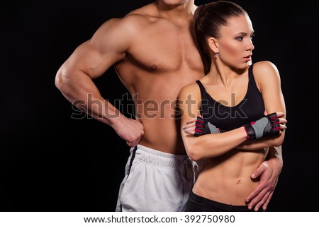 Aesthetic fit girl and bodybuilder. Bodybuilder next to lean woman. Building muscle and losing fat. Fitness models in perfect shape. - stock photo
