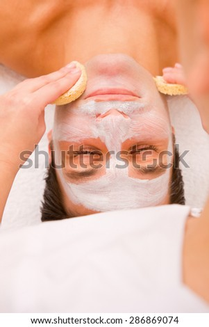 Aesthetician cleaning face with sponge - stock photo