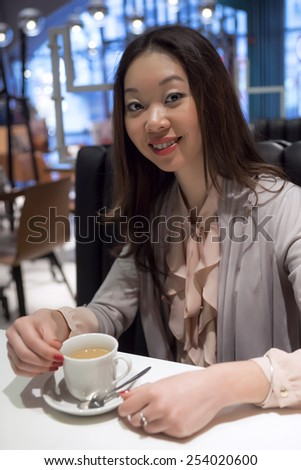 Affable beautiful Korean woman with a cup of coffee - stock photo