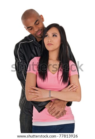 Affectionate African American guy embracing sceptical-looking Asian girl.
