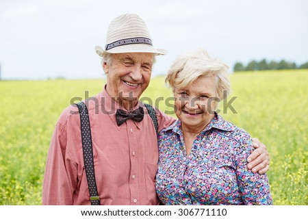 Affectionate and happy seniors looking at camera outdoors - stock photo