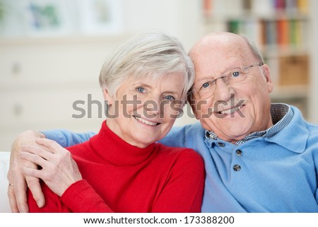 Affectionate attractive elderly couple sitting together on a couch in the living room with their arms around each other smiling at the camera - stock photo