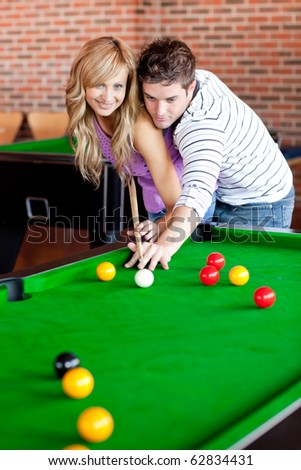 Affectionate boyfriend learning his girlfriend how to play pool in a club - stock photo