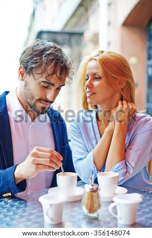 Affectionate couple drinking coffee together at a cafe - stock photo