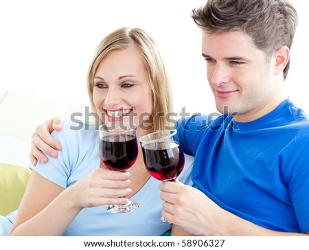 Affectionate couple drinking wine sitting on a sofa in the living room - stock photo