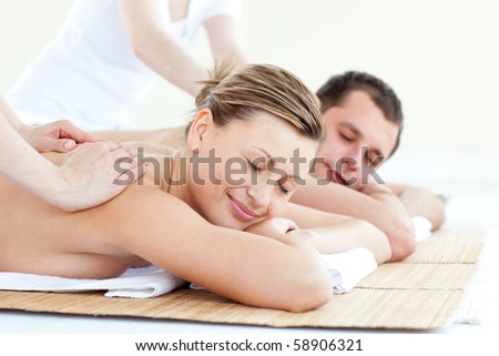 Affectionate couple having a back massage with closed eyes in a spa