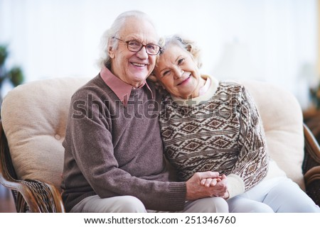 Affectionate couple in casualwear having rest at home - stock photo