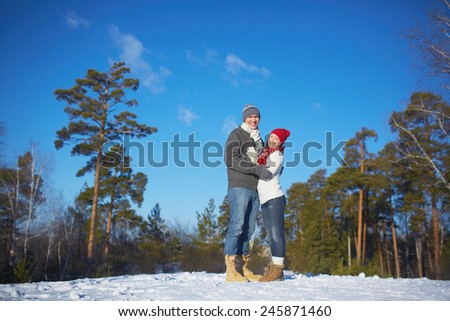 Affectionate couple in knitted winterwear enjoying weekend in forest - stock photo