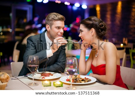 Affectionate couple in restaurant,  him feeding she - stock photo