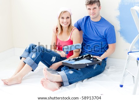 Affectionate couple painting a room together in their new home