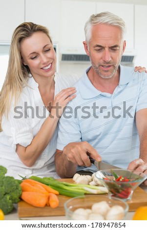 Affectionate couple preparing dinner together at home in the kitchen