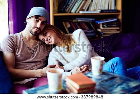 Affectionate couple resting on sofa and enjoying each other - stock photo