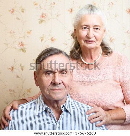 Affectionate couple smiling at camera at home in living room