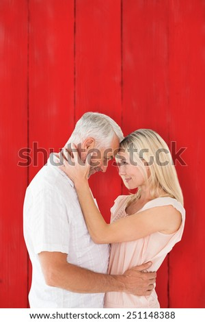 Affectionate couple standing and hugging against red wooden planks - stock photo
