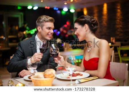 affectionate couple toasting at restaurant in romantic atmosphere - stock photo