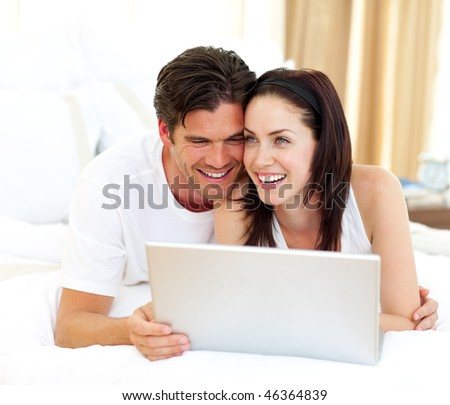 Affectionate couple using laptop lying on the bed - stock photo