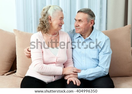 Affectionate elderly couple with beautiful beaming friendly smiles posing together in a close embrace in their living room. Portrait of a candid senior couple enjoying their retirement. - stock photo