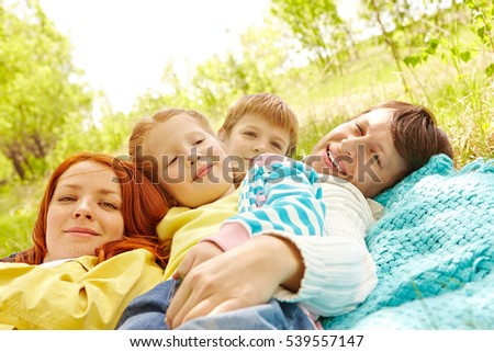Affectionate family of four relaxing on blanket in park