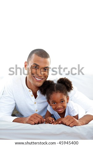 Affectionate father and his daughter having fun lying on a bed