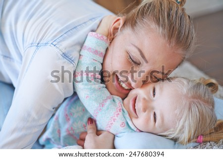 Affectionate female and her daughter in embrace - stock photo