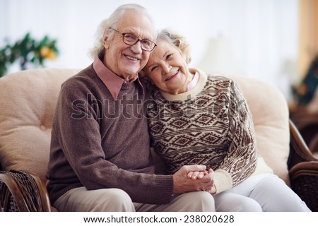 Affectionate grandparents having rest at home - stock photo