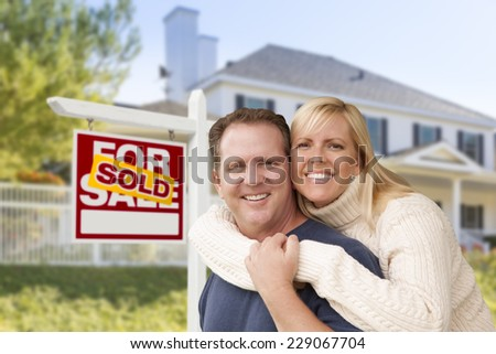 Affectionate Happy Couple in Front of New House and Sold For Sale Real Estate Sign. - stock photo