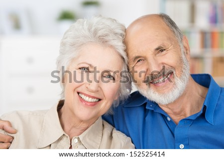 Affectionate happy retired couple with their heads together in a close embrace smiling at the camera - stock photo