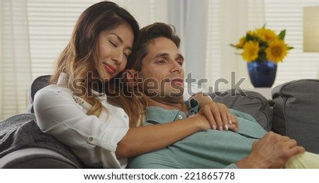 Affectionate interracial couple sitting on couch - stock photo