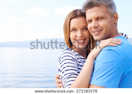 Affectionate man and woman enjoying summer vacation by sea