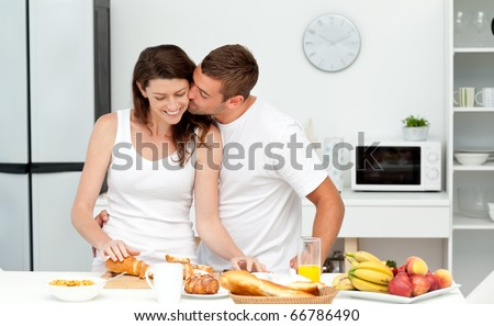Affectionate man kissing his girlfriend while cutting bread for breakfast in the kitchen