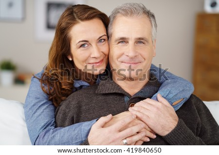 Affectionate married middle-aged couple relaxing at home on the sofa with the wife hugging her husband from behind, both smiling at camera - stock photo