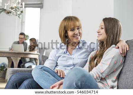 affectionate mother and daughter sitting on sofa with family in background