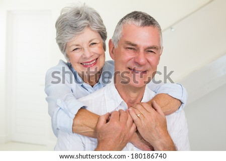 Affectionate retired couple smiling at camera at home in living room - stock photo