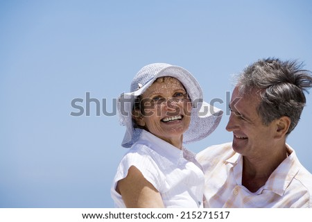 Affectionate senior couple embracing on beach, smiling, side view