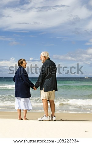 Affectionate senior couple holding hands and conversing at the beach - stock photo