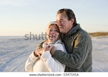 Affectionate senior couple in sweaters together on beach - stock photo
