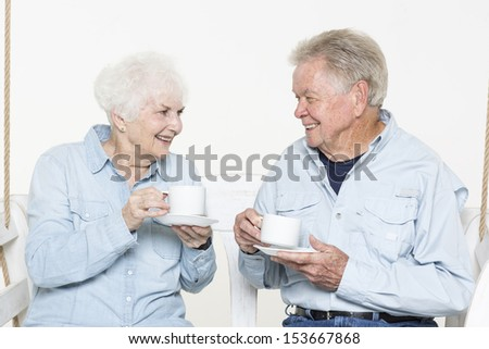 Affectionate senior couple is having coffee together - stock photo