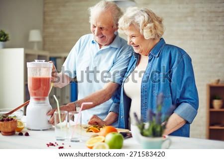 Affectionate senior couple making fruit smoothie - stock photo