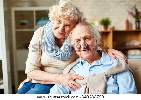 Affectionate seniors in casual-wear looking at camera - stock photo
