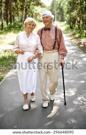 Affectionate seniors in smart casual going down park road - stock photo