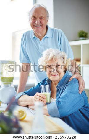 Affectionate seniors looking at camera in the kitchen